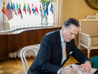 Ambassador at Large, H.E. Eitvidas Bajarūnas signs the document in Helsinki